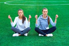 Two girl sports doing stretching fitness exercises in a city park on green grass. Yoga poses. morning Royalty Free Stock Photos