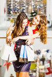 Two girl standing with bags in dresses hugging and laughing at the mall. Happiness concept, shopping, friendship Royalty Free Stock Photos