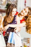 Two girl standing with bags in dresses hugging and laughing at the mall. Happiness concept, shopping, friendship Royalty Free Stock Photo