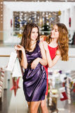 Two girl standing with bags in dresses hugging and laughing at the mall. Happiness concept, shopping, friendship Stock Image