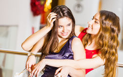 Two girl standing with bags in dresses hugging and laughing at the mall. Happiness concept, shopping, friendship Stock Images