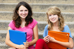 Two girl students at school smiling. Two happy and smiling teenager girls, students or youn women, holding books while sitiing on the stairs at school Royalty Free Stock Photos