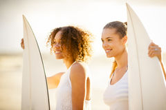 Two girl surfers at sunset. Two girl surfers standing on the beach at sunset Stock Photo