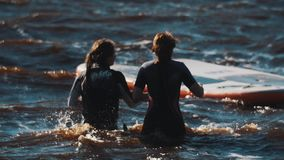 Two girl in swimming suits walking in wavy water toward floating surfing boards. On summer sunny windy day, slow motion stock footage