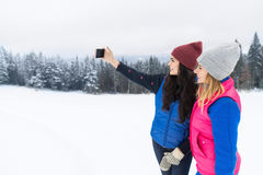 Two Girl Taking Selfie Photo On Smart Phone Snowy Mountain Young Woman Winter Snow. Holiday Vacation Stock Photography