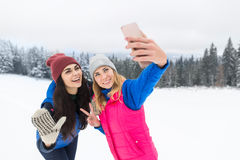 Two Girl Taking Selfie Photo On Smart Phone Snowy Mountain Young Woman Winter Snow. Holiday Vacation Royalty Free Stock Images