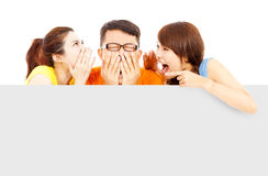 Two girl talk to young man about surprising news Stock Photo