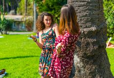 Two girl talking and laughing on their smartphone stock photo