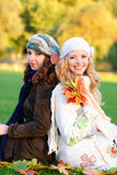 Two girl under the maple tree Stock Image