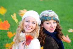 Two girl under the maple tree royalty free stock image