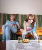 Two girl watching TV. Two girls watching TV in living room, with two juice and some snack on table. Concept of entertainment, TV, friendship, relaxing Stock Photos