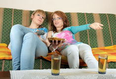 Two girl watching TV and talking. Two girls watching TV and talking at home, with two juice and some snack on table. Concept of entertainment, TV, friendship Stock Images