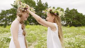 Two girl wearing floral wreath having fun on blooming meadow at summer day. Happy girl teenager playing with flower. Wreath on summer field in countryside stock footage
