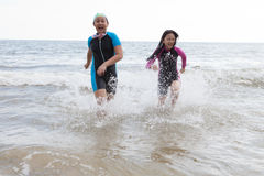 Two girl wearing wet suit  playing on sea beach with happiness e Royalty Free Stock Images