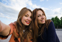 Two girlfriend smiling  make Selfie. Two girlfriend smiling in the park make Selfie Stock Photography