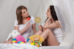 Two girlfriend with sugar candies. Royalty Free Stock Photos