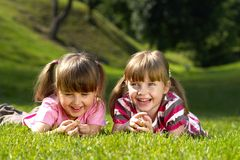 Two girlfriends. Two little girls lying on the grass in the park Stock Photography