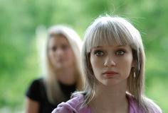 Two girlfriends. The portrait of the young beautiful girl in the foreground, behind it costs its girlfriend Royalty Free Stock Images