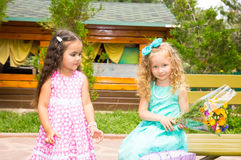 Two girlfriends. Adorable little children with bouquet of flowers on happy birthday. Kid in park stock photo