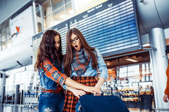 Two girlfriends at the airport waiting for the flight.Art proces Stock Images
