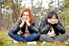 Two girlfriends at the autumn park. Royalty Free Stock Photos