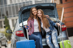 Two girlfriends with the bags near the car. Happy girlfriends, two beautiful young brunette women with long straight hair, nice smile, dressed in blue jeans Stock Photos