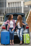 Two girlfriends with the bags near the car. Happy girlfriends, two beautiful young brunette women with long straight hair, nice smile, dressed in blue jeans Stock Photo