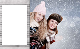 Two girlfriends behind a wooden board Royalty Free Stock Photography