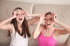 Two girlfriends being silly by making goggles with fingers. Two young laughing girlfriends being silly, constructing goggles with fingers circling their eyes Royalty Free Stock Images