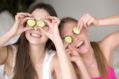 Two girlfriends being silly by putting cucumbers on their eyes. Two young smiling girlfriends being silly, putting cucumbers on their eyes and making funny Stock Photography