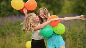 Two girlfriends best friends hugging with colorful balls. Two young girlfriends best friends hugging with colorful balls. Two blondes stock footage