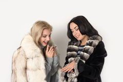 Two girlfriends blonde and brunett in short fur coats watch a r. Ing stock images