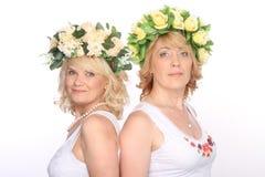 Two girlfriends blonde women in wreaths, smiling, standing backs. Two girlfriends blonde women in wreaths, smiling back to back stock photos