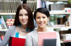 Two girlfriends with books at the library Royalty Free Stock Photo