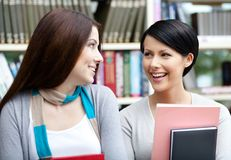 Two girlfriends with books look at each other Stock Image