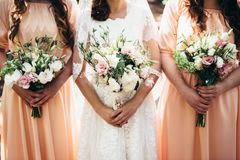 Two girlfriends and a bride hold beautiful wedding bouquets in t stock photos