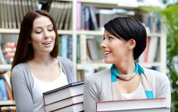 Two girlfriends carry books. Two girlfriends carry piles of books at the library Royalty Free Stock Photo