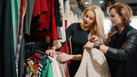 Two young women choose clothes in the store. Two girlfriends choose clothes in the store during shopping stock video