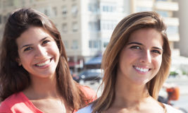 Two girlfriends in the city laughing at camera Royalty Free Stock Photo