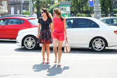 Two girlfriends crossing the road Royalty Free Stock Photo