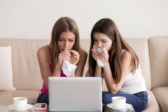 Two girlfriends crying while watching sad movie. Two sentimental women friends upset crying and wiping tears with handkerchiefs while watching dramatic, sad Stock Photos