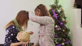 Two sisters have fun during decorating Christmas tree. Two girlfriends decorates Christmas tree at home. Pretty girls hangs colorful garlands on ach other. Two stock video