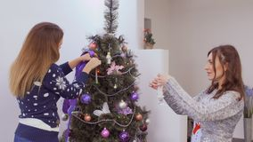 Girls decorate christmas tree. Two girlfriends decorates Christmas tree at home. Pretty girls hangs toys and puts the colorful garlands on the fir-tree. Two stock video
