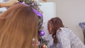 Two young girls decorates Christmas tree. Two girlfriends decorates Christmas tree at home. Pretty girls hangs toys and puts the colorful garlands on the fir stock video footage