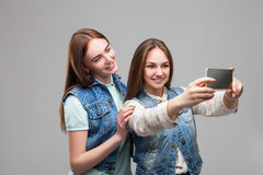 Two girlfriends in denum jackets makes selfie Royalty Free Stock Photos