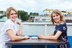 Two girlfriends on different side of table Royalty Free Stock Photos