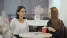 Two girlfriends discuss their hair relaxing in cafe. Young attractive workers sit in the co-working space at the table. Handsome women sit at the cafe at work stock footage