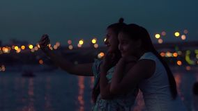 Two girlfriends do selfie on a background of a night city. slow motion. Two girlfriends do selfie using the phone on a background of a night city. slow motion