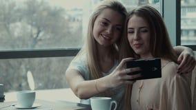 Two girlfriends do selfie in cafe stock video