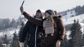 Two girlfriends do selfie on the mountain. Two smiling girlfriends do selfie on the mountain in the winter using digital tablet stock video